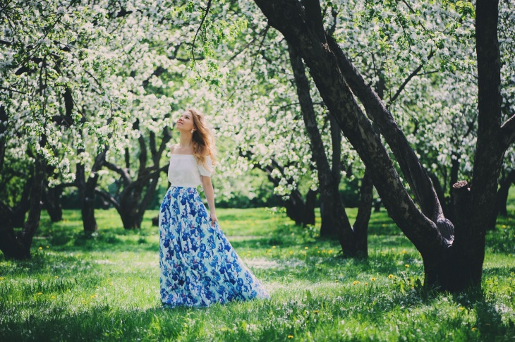beautiful young woman in floral maxi skirt walking in spring garden